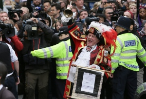 Tony Appleton, a town crier, announces to the assembled media the birth of the royal baby, outside the Lindo Wing, St. Mary's Hospital, London, Saturday, May 2, 2015. Kate, the Duchess of Cambridge, has given birth to a baby girl, royal officials said Saturday. (AP/Tim Ireland)