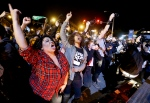 Protesters demonstrate as a curfew imposed in the aftermath of rioting following Monday's funeral for Freddie Gray goes into effect Friday, May 1, 2015, in Baltimore. (AP Photo/David Goldman)