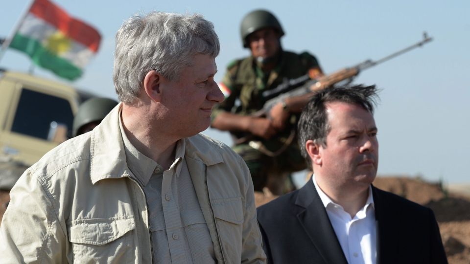 A Kurdish soldier sits in the background as Prime Minister Stephen Harper and Minister of Defence Jason Kenney visit members of the Advise and Assist mission, approximately 6 km from active ISIL fighting positions, 40 km west of Erbil, Iraq, on Saturday, May 2, 2015. (Sean Kilpatrick / THE CANADIAN PRESS)
