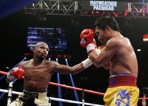 Floyd Mayweather Jr., left, punches Manny Pacquiao, from the Philippines, during their welterweight title fight on Saturday, May 2, 2015 in Las Vegas. (AP Photo/Isaac Brekken)