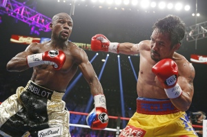 Manny Pacquiao, from the Philippines, right, throws a right against Floyd Mayweather Jr., during their welterweight title fight in Las Vegas on Saturday, May 2, 2015. (AP / John Locher)