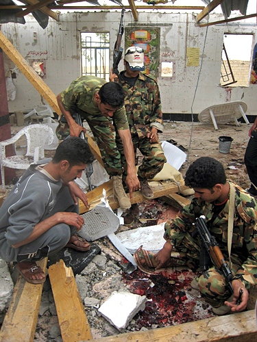 Iraqi soldiers inspect the damage caused by a suicide bomber attack on a highway near Ramadi, 115 kilometers (70 miles) west of Baghdad, Iraq, Monday, April 23, 2007. (AP Photo)