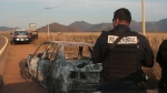 In this file photo, federal police stand next to a bullet riddled and burned car after a criminal gang ambushed a police convoy near the town of Soyatlan, near Puerto Vallarta, Mexico, Monday, April 6, 2015. (AP)
