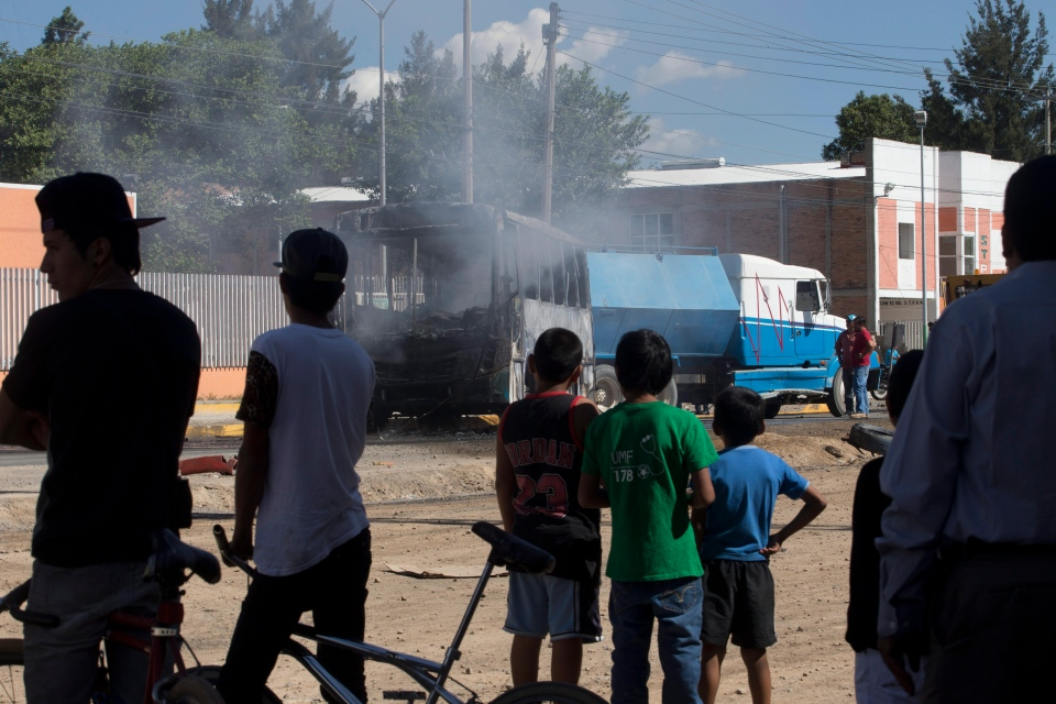 People watch as a torched passenger bus smolders after it was extinguished by firefighters in Guadalajara, Mexico, Friday, May 1, 2015. (AP / Refugio Ruiz)