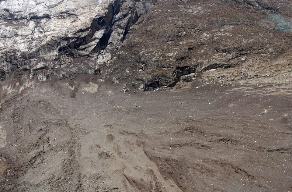 In this Tuesday, April 28, 2015 photo provided by Medecins Sans Frontieres, a lone house, center, is visible after a quake-triggered mudslide wiped out the village of Langtang, Nepal. (Medecins Sans Frontieres via AP)
