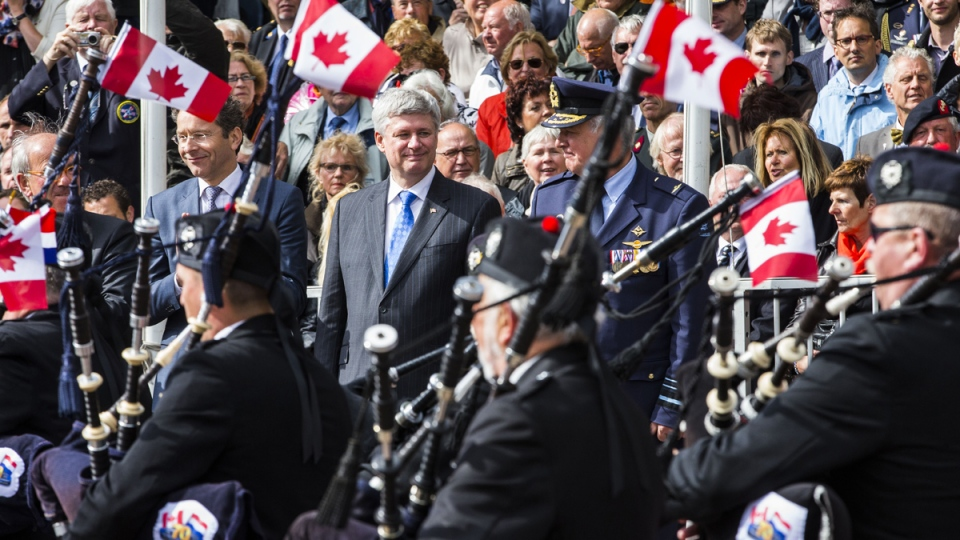 Prime Minister Stephen Harper, centre, watches a parade in Wageningen, Netherlands, Tuesday May 5, 2015. (AP / Vincent Jannink)