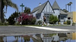 A house is reflected in a puddle of water from an irrigated front yard in San Diego on July 9, 2014. (AP / Gregory Bull)