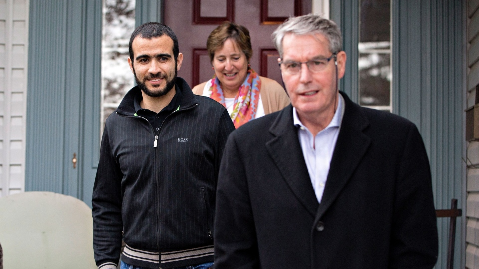 Omar Khadr, left to right, Patricia Edney and his lawyer Dennis Edney come out of the house to speak to media after being released on bail in Edmonton, Alta., on Thursday, May 7, 2015. (Jason Franson / THE CANADIAN PRESS)
