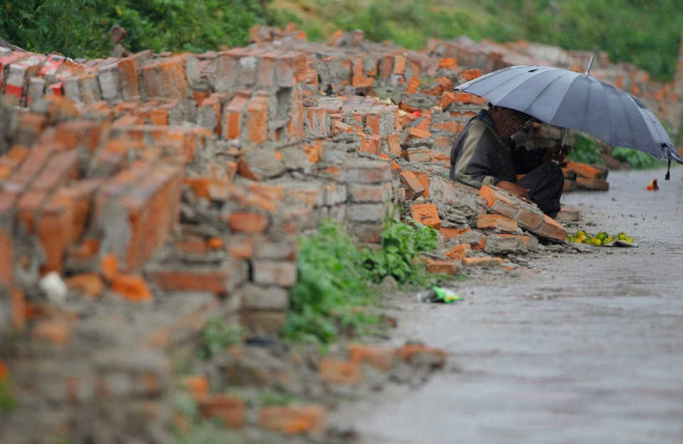 A Nepalese street vendor waits for customers in front of a broken wall in Kathmandu on Saturday, May 9, 2015. (AP / Niranjan Shrestha)