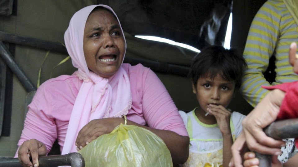 Ethnic Rohingya women and children whose boats were washed ashore on Sumatra Island board a military truck to be taken to a temporary shelter in Seunuddon, Aceh province, Indonesia on May 10, 2015. (AP / S. Yulinnas)