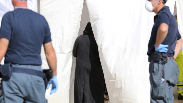 A migrant enters a Red Cross tent
