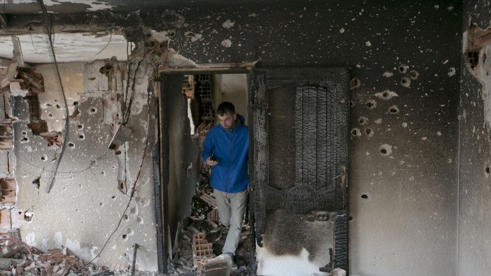 A resident inspects the damage in a neighborhood where a battle took place over the weekend involving the police and an armed group, in northern Macedonian town of Kumanovo, Monday, May 11, 2015. (AP / Visar Kryeziu)