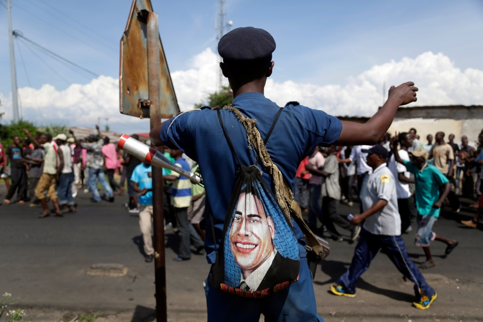 A police officer stands on patrol as protesters march through Buhumbura in Burundi. The army negotiated with over 2000 protesters to allow delivery trucks to enter the city. (AP / Jerome Delay)