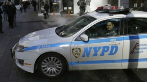A policeman looks out the window of his patrol car in Times Square in New York, Thursday, Jan. 8, 2015. (Seth Wenig/AP)