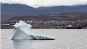 Ice floats past a cargo ship and the hamlet of Pond Inlet Sunday August 24, 2014. (Adrian Wyld/THE CANADIAN PRESS)