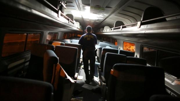 A crime scene investigator looks inside a train car after a train wreck, Tuesday, May 12, 2015, in Philadelphia. (AP / Joseph Kaczmarek)
