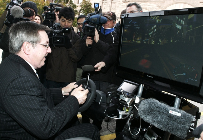 Ontario Transportation Minister Jim Bradley drives in a simulation car ride called D.U.M.B. (Distractions Undermining Motorists Behaviour) while trying to make a phone call at an announcement in Toronto, Tuesday, Oct. 28, 2008. (Jim Ross / THE CANADIAN PRESS)