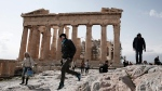 A tourist jumps in front of the ancient Parthenon temple at the Acropolis hill, in Athens, on Tuesday, Feb. 17, 2015.  (AP /Petros Giannakouris)