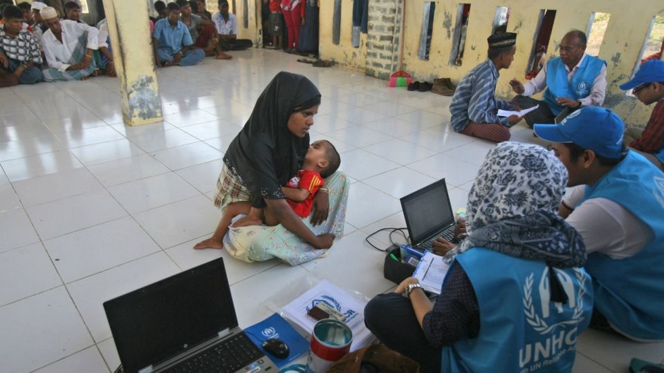 An ethnic Rohingya woman carries her baby as she answers questions from UNHCR workers at a temporary shelter in Lapang, Aceh province, Indonesia, Thursday, May 14, 2015. (AP / Binsar Bakkara)