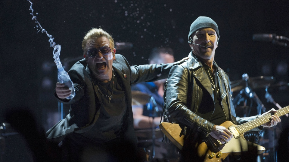U2 lead singer Bono throws water at the crowd while the Edge looks on as they perform in Vancouver, B.C. on May, 14, 2015. (Jonathan Hayward / THE CANADIAN PRESS)