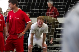 Prince Harry, centre, sticks his tongue out during a 5-a-side soccer game at The Cloud, a multi-purpose venue in Auckland, New Zealand on Saturday, May 16, 2015. Prince Harry is on the last day of his visit to New Zealand. (Michael Craig / Herald on Sunday via AP)
