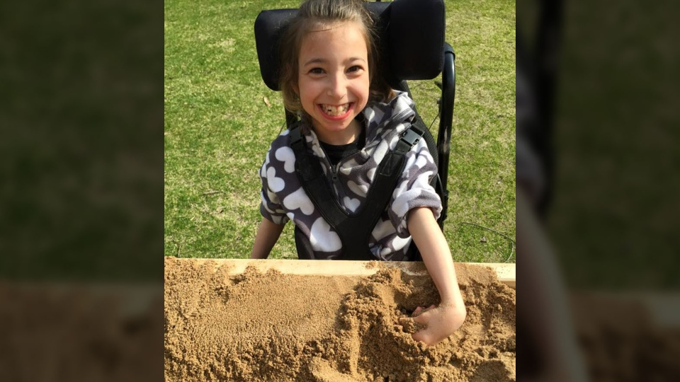 Cadence Flaata plays with her accessible sandbox (Facebook/Northern Lights Adaptations)