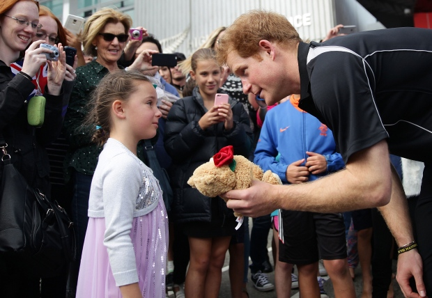 Prince Harry is given a teddy bear from Maddison Hailes during a visit to the Auckland University of Technology Millennium Institute in Auckland, New Zealand, Saturday, May 16, 2015. (AP / Doug Sherring)