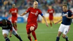 Toronto FC's Michael Bradley (4) sets up his scoring kick between New England Revolution's Teal Bunbury (10) and Scott Caldwell (6) during the second half of an MLS soccer game in Foxborough, Mass., Saturday, May 16, 2015. (AP Photo / Michael Dwyer)