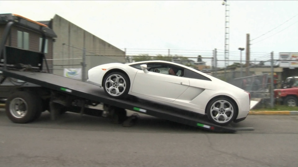 A white Lamborghini impounded for doing twice the posted speed limit on the Trans-Canada Highway in Victoria, B.C. is loaded onto a flatbed truck. Saturday, May 16, 2015. (CTV)