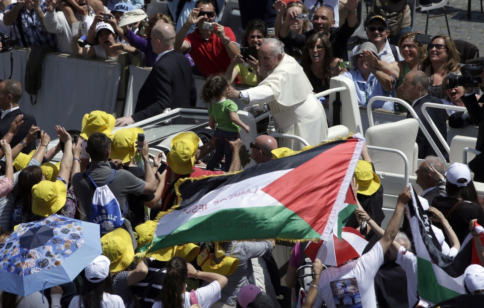 Pope Francis caresses a child as he greets faithful in St. Peter's Square at the Vatican, Sunday, May 17, 2015. (AP / Alessandra Tarantino)
