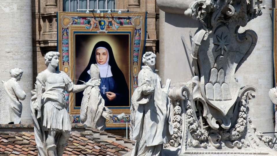 A tapestry showing St. Marie Alphonsine Ghattas hangs from a balcony of St. Peter's Basilica at the Vatican, Sunday, May 17, 2015. (AP / Alessandra Tarantino)