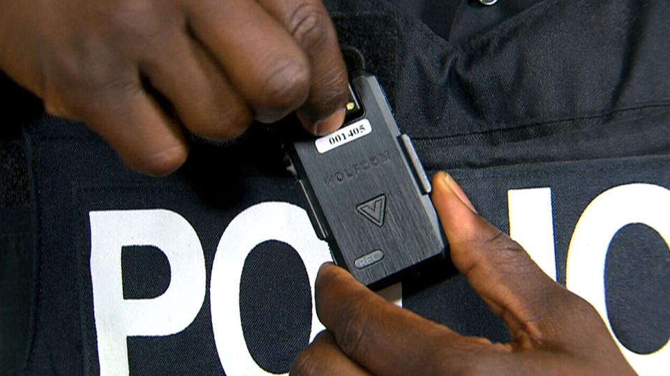 An officer shows off one of the lapel-mounted body cameras that members of the Toronto Police Service will wear as part of a pilot project during a press conference on Friday, May 15, 2015.