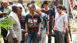 Plain clothes police officers accompany Chinese nationals accused of illegal mining out of a courtroom, following a hearing in Accra, Ghana, Monday May 18, 2015. (AP Photo/Christian Thompson)