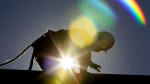 In this July 6, 2010 file photo, a construction worker is backlit from the morning sun while working on a roof in the heat in Chapel Hill, N.C. (Gerry Broome / AP Photo)