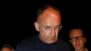 Douglas Garland is escorted into a Calgary police station in Calgary, Alta., Monday, July 14, 2014. (Jeff McIntosh/The Canadian Press)