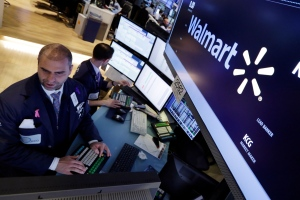Specialist Philip Finale, left, works at the post that handles Wal-Mart, on the floor of the New York Stock Exchange, Tuesday, May 19, 2015. Wal-Mart Stores Inc. reported sluggish sales and a 7 percent drop in first-quarter profit. (AP / Richard Drew)