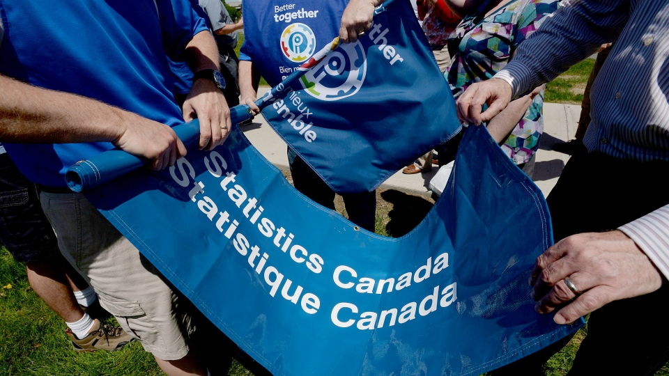 Staff members from Statistics Canada wrap up a banner following a rally to protest the muzzling of Canada's public scientists at Tunney's Pasture in Ottawa on Tuesday, May 19, 2015. (Sean Kilpatrick / THE CANADIAN PRESS)