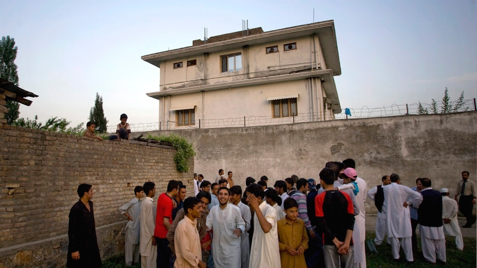 In this May 3, 2011 file photo, local residents gather outside a house, where al Qaeda leader Osama bin Laden was caught and killed in Abbottabad, Pakistan. (AP / B.K.Bangash)