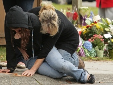 Orion Hutchinson's mother Judith, right, and an unidentified young woman break down after laying flowers at a makeshift memorial in Delta, B.C., on Wednesday October 29, 2008. (THE CANADIAN PRESS/Darryl Dyck)