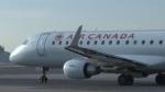 An Air Canada plane taxis on a runway.