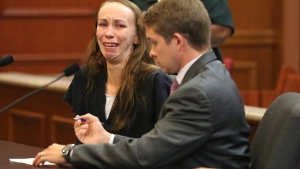 Heather Hironimus, sitting with her attorney Thomas Hunker, breaks down as she signs consent for her 4-year-old son to be circumcised, during a hearing, in Delray Beach, Fla., Friday, May 22, 2015. (Amy Beth Bennett / South Florida Sun-Sentinel via AP)