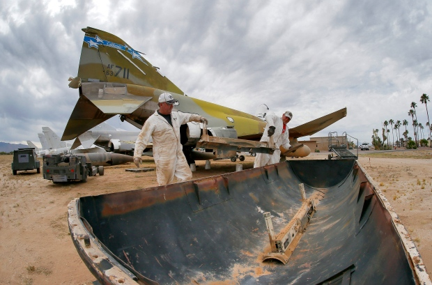 Phil Kovaric and Dennis Varney remove the missile rails from an F-4 Phantom slated for destruction at the 309th Aerospace Maintenance and Regeneration Group boneyard in Tucson, Ariz. The 309th is the United States Air Force's aircraft and missile storage and maintenance facility and provides long and short-term aircraft storage, parts reclamation and disposal. (AP / Matt York)