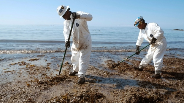 Crews from Patriot Environmental Services collect oil-covered seaweed and sand from the shoreline at Refugio State Beach, north of Goleta, Calif., Wednesday, May 20, 2015. (AP / Michael A. Mariant)