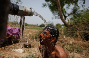 India also suffered through a heat wave in May, 2015. Here, an Indian man takes bath under the tap of a water tanker in Ahmadabad, India, Thursday, May 21, 2015. (AP / Ajit Solanki)