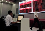In this May 12, 2015 photo, a worker checks documents on his computer as his colleague walks past an electronic board displaying the carbon trading index, left, at the Beijing Environmental Exchange office in Beijing, China. (AP / Andy Wong)