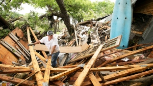 Keith McNabb looks at the damage to his friend Mike Cook's house on Stone Canyon Street on the banks of the Blanco River near Wimberley, Texas on Sunday May 24, 2015. (Jay Janner / Statesman.com)