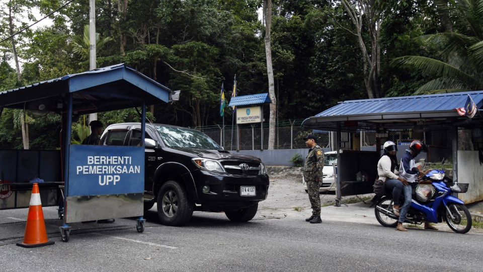 Malaysian Anti-Smuggling Unit officers check on vehicles at the entry point of Malaysia - Thailand border in Wang Kelian, Malaysia on May 24, 2015. Malaysia authorities said Sunday that they have discovered graves in more than a dozen abandoned camps used by human traffickers on the border with Thailand. (AP / Joshua Paul)