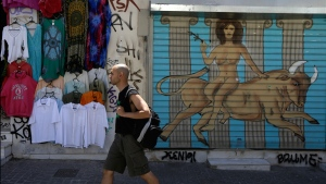 A pedestrian passes graffiti in Athens, Greece, on May 25, 2015. (AP / Thanassis Stavrakis)