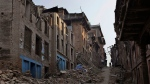 A Nepalese man walks through a path cleared with rubble of damaged houses one month after the deadly 7.8 magnitude earthquake in Kathmandu, Nepal Monday, May 25, 2015. (AP / Niranjan Shrestha)
