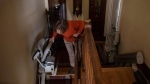 Linda Jarrett, who suffers from multiple sclerosis, maneuvers herself between stair lifts in her home in Kitchener, Ont., on Tuesday, February 10, 2015. (THE CANADIAN PRESS/Chris Young)